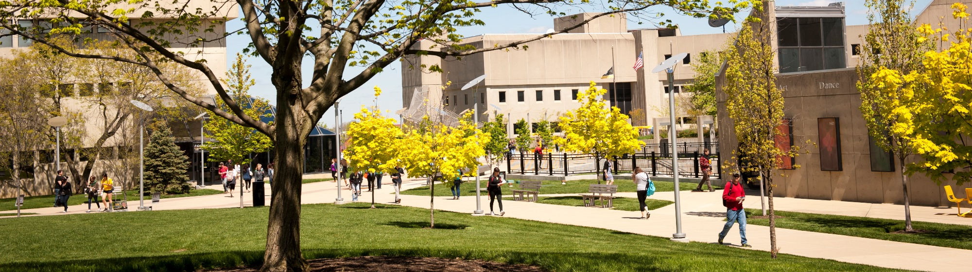 NKU students walking with campus buildings in the background.