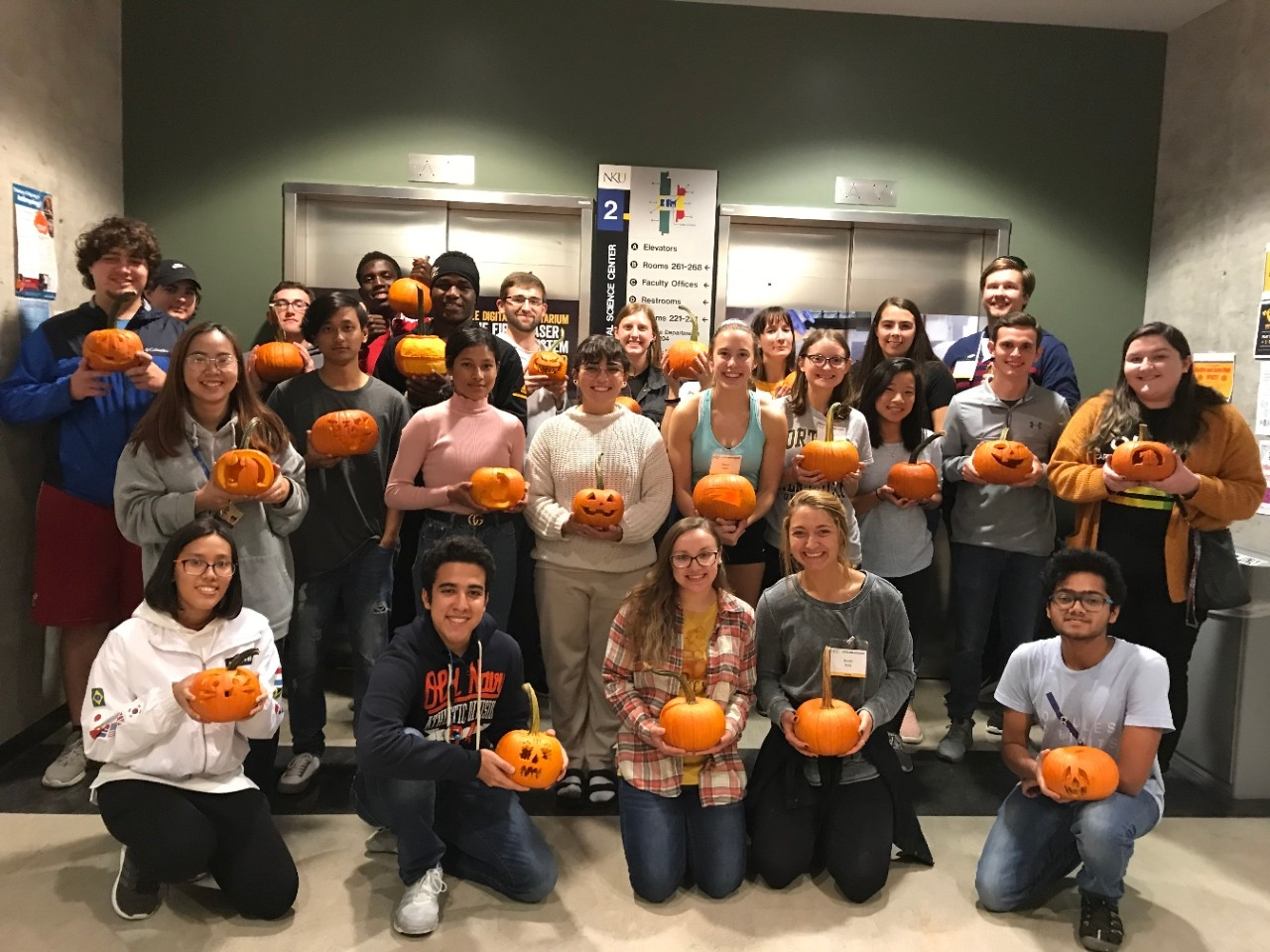 STEM students posing with their carved pumpkins at a pumpkin carving event