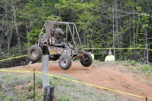 student driving the Baja SAE vehicle on a dirt trail
