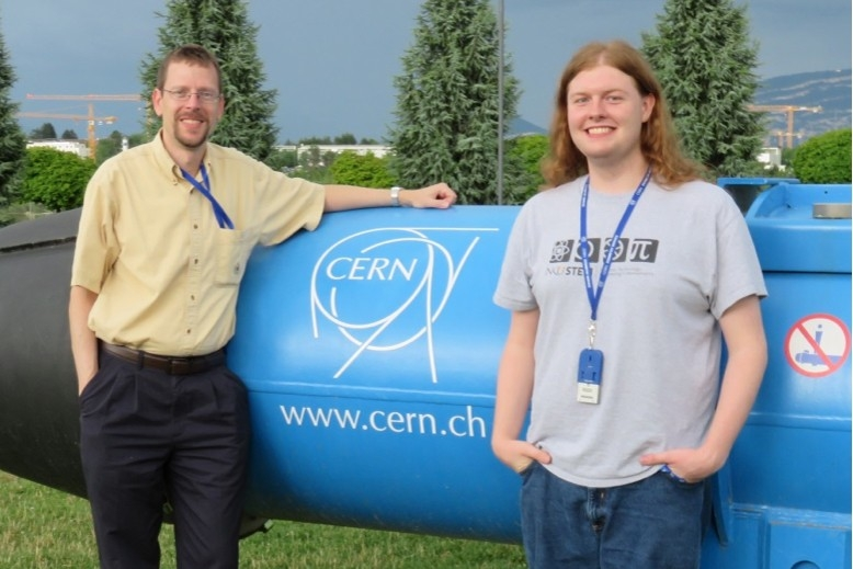 A student and faculty member pose in front of a CERN sign