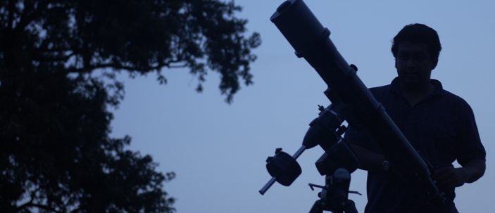 The silhouette of a student with a telescope at twilight