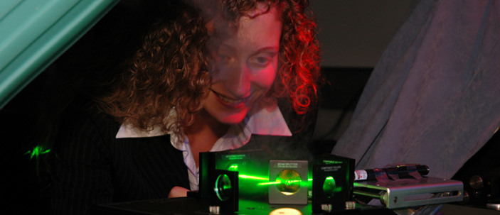 A student looking at a physics experiment using a green laser