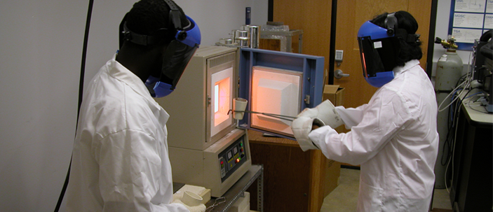 Researchers remove material from a research oven