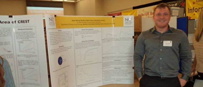 A student standing in front of his research poster
