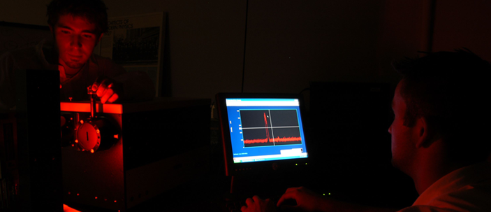 Students looking at equipment readings on a monitor