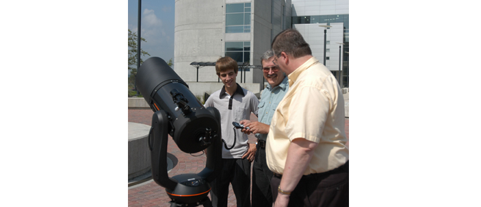 Faculty demonstrating how to use a telescope outside Science Center