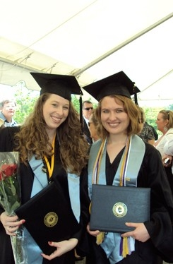 Two psychology graduates with their diplomas