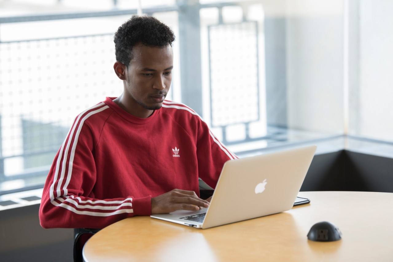 Male student on Mac computer