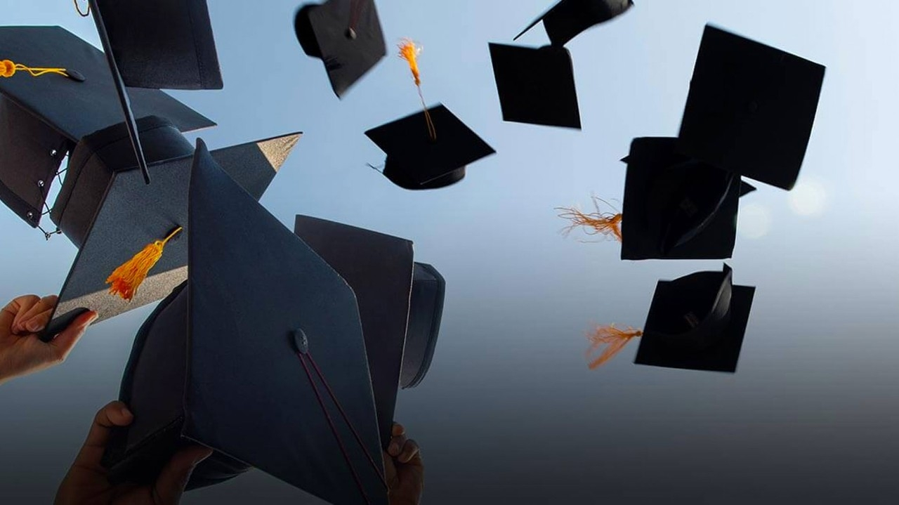 Graduation image showing mortarboards being thrown into the air.